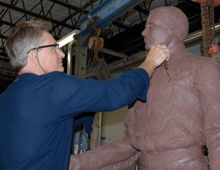 Sculptor Tom Bollinger puts finishing touches on the face.